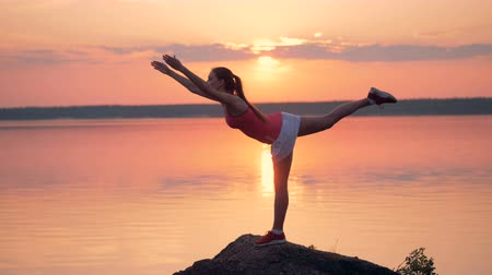 ativo : Gorgeous lady is doing exercises on a hill near a lake during sunrise