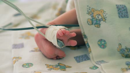 vital signs : Close up of babys moving legs with a sensor connected to one of them