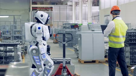 robot : A man activates droid at a factory. A worker switches on a robot to make it pull a heavy cart with metal sheets.