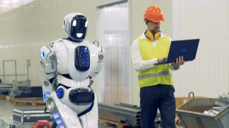 robots : A human and a robot walk together at a warehouse, close up.