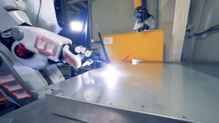 forro : White robot uses a welding tool, close up. Special robot works at a plant, welding metal sheets.