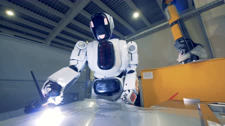 сварщик : A droid works with welding machine, close up. One robot welds a metal sheet at a factory.