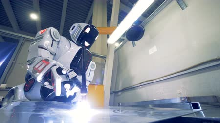 droid : Humanoid with a welding equipment works at a plant, close up. Stock Footage