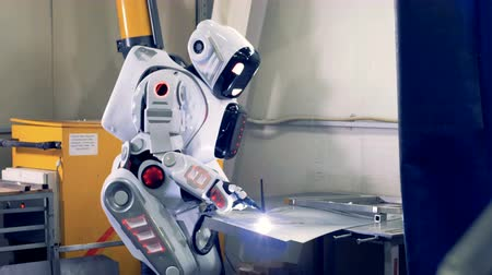 forro : Android uses factory equipment to work with metal, close up. One robot works at a factory, welding with a tool.