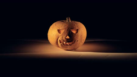 wicked : Illuminated carved traditional jack-o-lantern in a dark room. Halloween pumpkin in dark.