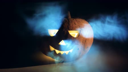 uğursuz : Clouds of smoke are wreathing around a halloween pumpkin. Scary carved halloween pumpkin