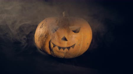 wicked : Smoke is getting ejected and then dissipating around a jack-o-lantern. Scary carved halloween pumpkin.