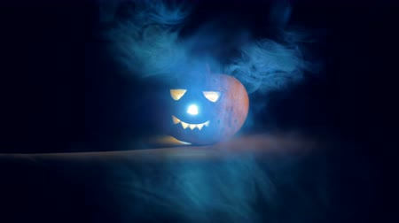 wicked : Dark room with clouds of mist and a glowing jack-o-lantern. Scary carved halloween pumpkin. Stock Footage