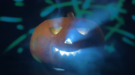 questão : Luminous decorative pumpkin in misty clouds at a party. Halloween pumpkin in dark.