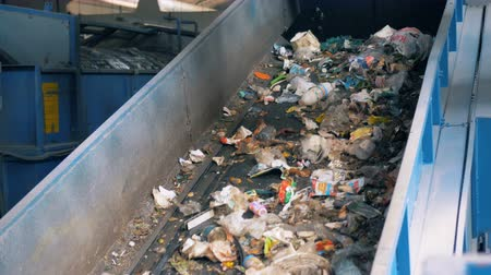 se movendo para cima : Moving conveyor at a garbage plant, close up. Trash goes on a conveyor after sorting.