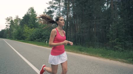 oturum : Forest road with a young lady running along it. Healthy slim young sportswoman running.
