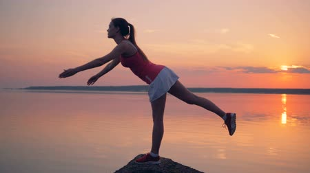 breathing fresh air : Exercising process of a pretty lady near a lake Stock Footage