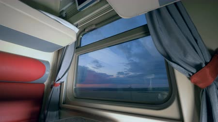 двухместная карета : Travelling by train concept. Evening scenery seen through the trains window in a cabin