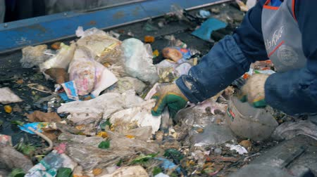 dumping : Stream of rubbish is getting sorted by a plant worker. Waste recycling plant. Stock Footage