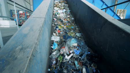 biodegradable : Conveyor belt filled with trash is moving upwards. Environmental pollution concept.