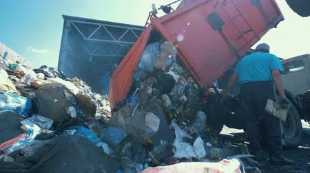 dumping : Litter is getting discarded from a truck in a scrapyard. Environmental pollution concept.