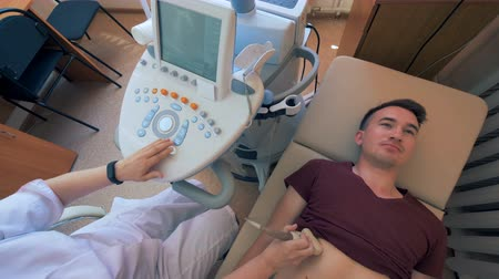 provést : Doctor is carrying out an ultrasonic procedure on a man Dostupné videozáznamy