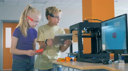 detay : A boy and a girl work in a laboratory inventing 3d printed robot. Stok Video
