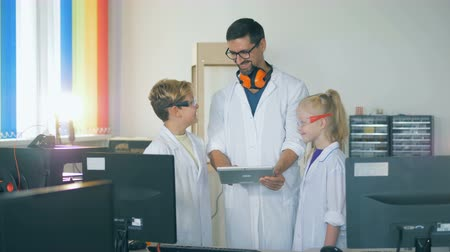 exited : A teacher and kids in a school laboratory room study technology. Stock Footage
