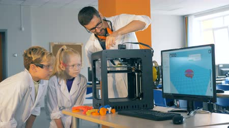 exited : Children and a school teacher work with a 3D printer in a laboratory, close up.