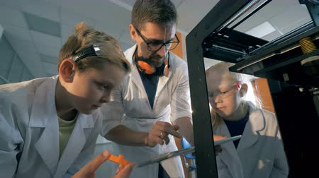академический : Teacher and pupils work with 3D printer using tablet.