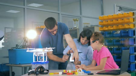 elsődleges : School children explore drone, copter, aircraft with a teacher in a technology class. Stock mozgókép