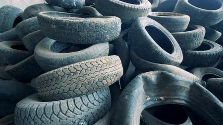 kerekek : Lots of used tires, close up. Old tires are piled at a dump. 4K.