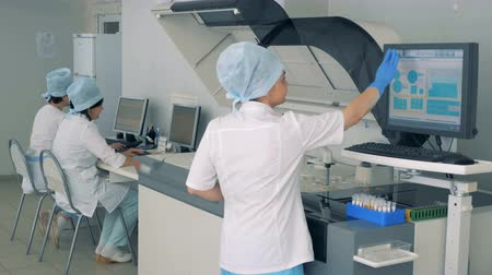 functioning : Female lab expert is manipulating biochemical analyzer on a touchscreen in a pharmacutical factory.