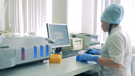 scanning : Female laboratory employee is preparing to scan test tubes Stock Footage
