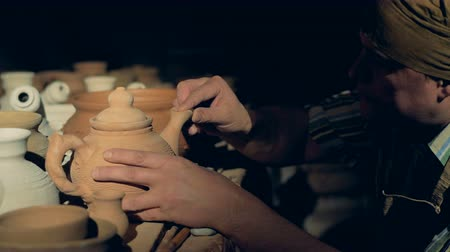 louça de barro : A pottery worker checks clay jar, touching its lip. Stock Footage