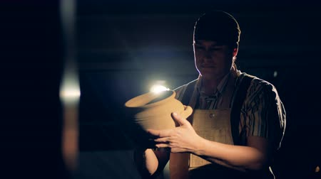 clay pot : Pottery maker holds a jug, looks at his clay piece of crockery. Stock Footage
