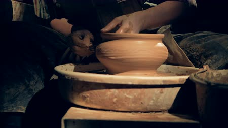 clay pot : A potter creates patterns on a vase, close up. Stock Footage