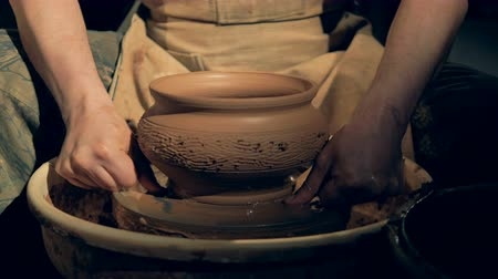 clay pot : Pottery worker removes a vase from a wheel, using a special line.