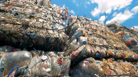 piled : Outdoors dumping site with multiple blocks of plastic trash. Recycle factory.