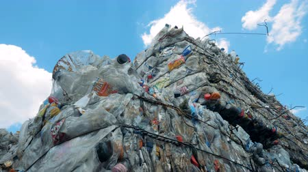 piled up : Used plastic and polyethylene compressed and storaged outdoors ready for recycling. Waste recycling concept. Stock Footage