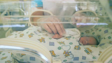 reanimation : A nurse takes babys hands, close up. Stock Footage