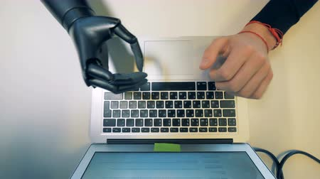 physically : Laptop keypad getting typed on by a Robotic cyborg arm.