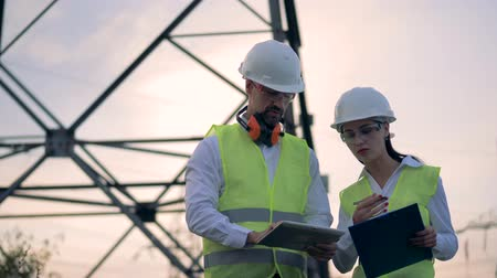 hard hat : Electricians talking near at the electrical substation. Stock Footage