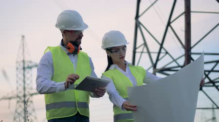 powerline : Workers at a high-voltage powerline working with a construction plan. Stock Footage
