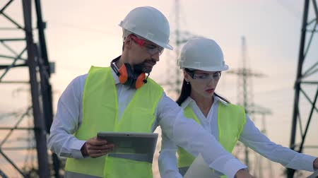 yelek : Male and female engineers in hard hat discussing construction project during energy substation inspection. Stok Video