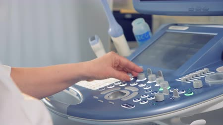 sonography : Female doctors hand manipulating an ultrasound console. Medical ultrasound scan.