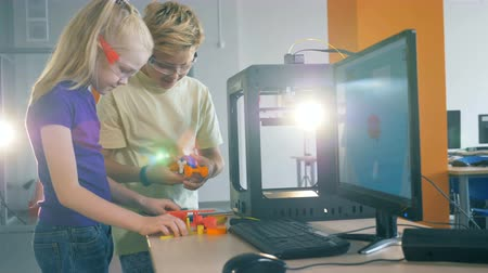 constructing : Two teen kids are trying to make up a device while being in a quantorium Stock Footage