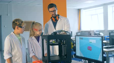 endowment : Interaction between a lab worker and two kids while managing 3D printing