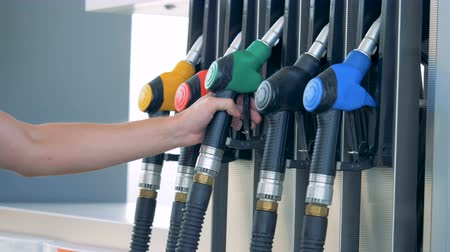 benzine : Person takes a nozzle for refilling at a filling station, petrol station, fuel station, gasoline station, refueling station.