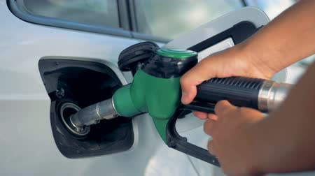 filling station : A man puts a nozzle in a car tank, close up. Stock Footage