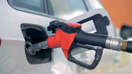 filling station : A red gas nozzle in a car tank, close up.