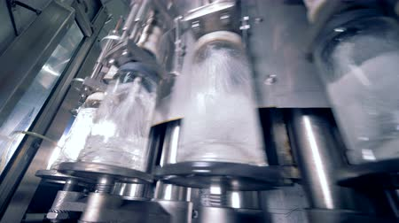 automated : Plant equipment filling lots of bottles, bottom view.