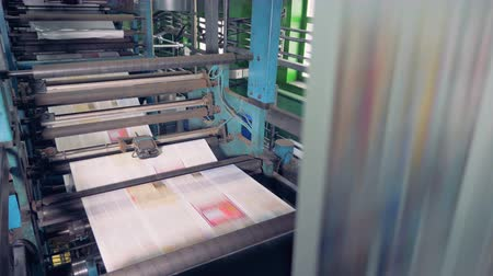 otisk : Machine works in printing office, close up. Newspaper printing equipment working.
