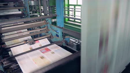 otisk : Colored papers on a printing machine. Newspaper printing equipment working. Dostupné videozáznamy