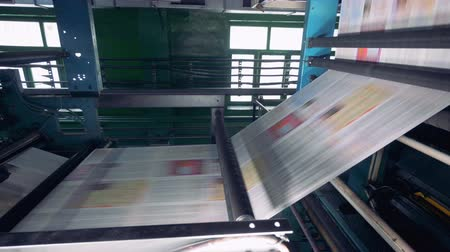 sheet : Fresh printed newspaper, magazines moving on a line at a printing office.